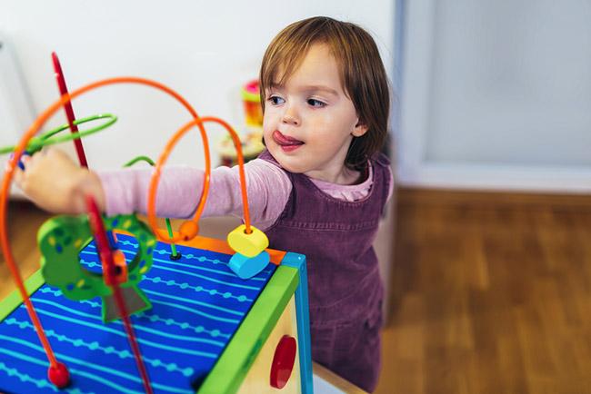 fillette joue avec cube d'activité